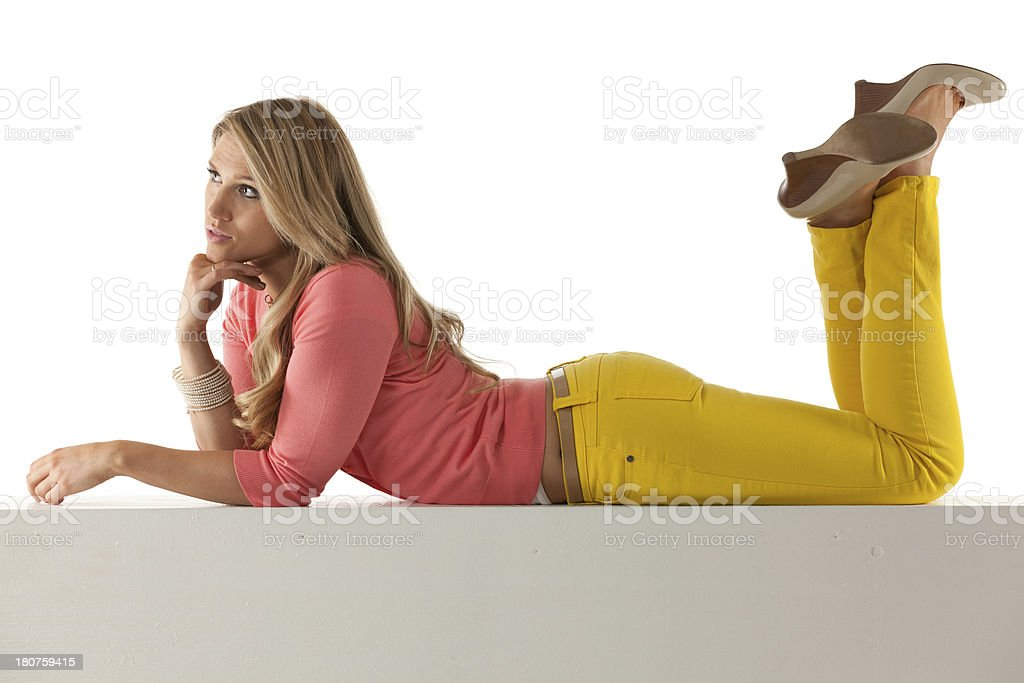 Attractive young female lying on ledge of a wall royalty-free stock photo