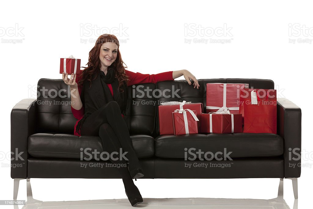 Attractive young female sitting on couch with gifts royalty-free stock photo