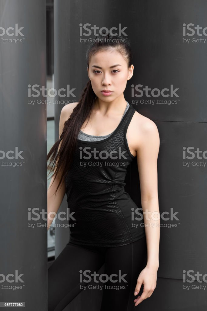 Attractive young fitness woman in sportswear posing and looking at camera stock photo