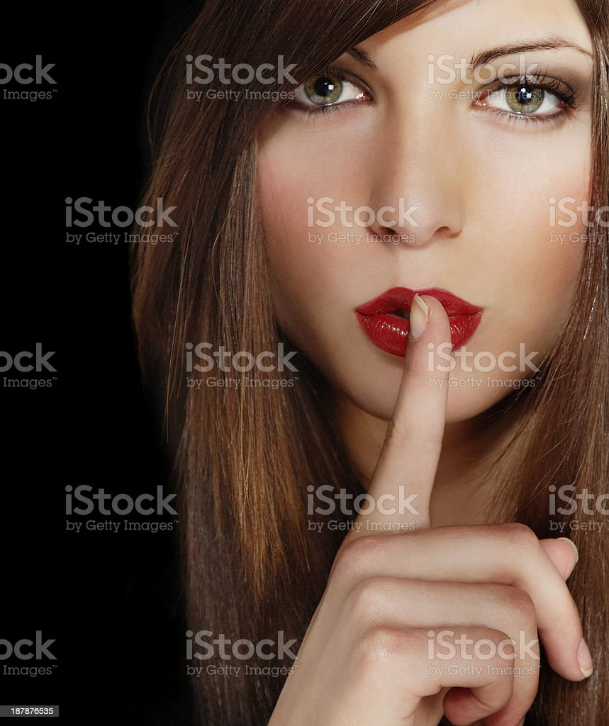 Attractive young girl with finger on lips and long hair stock photo