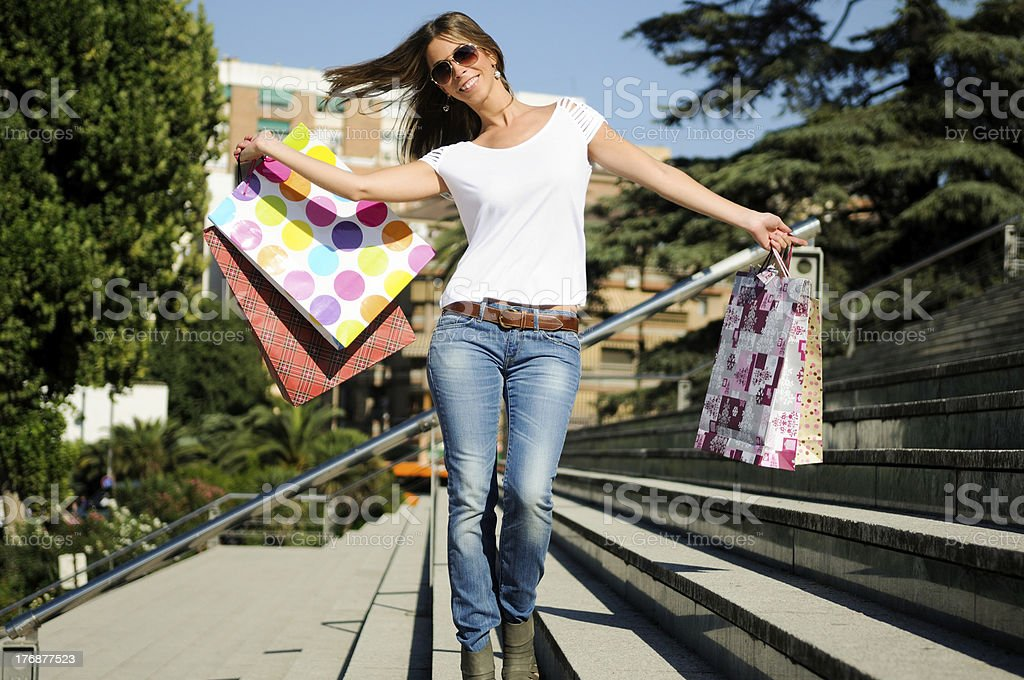 Attractive young girl with shopping bags on stair royalty-free stock photo
