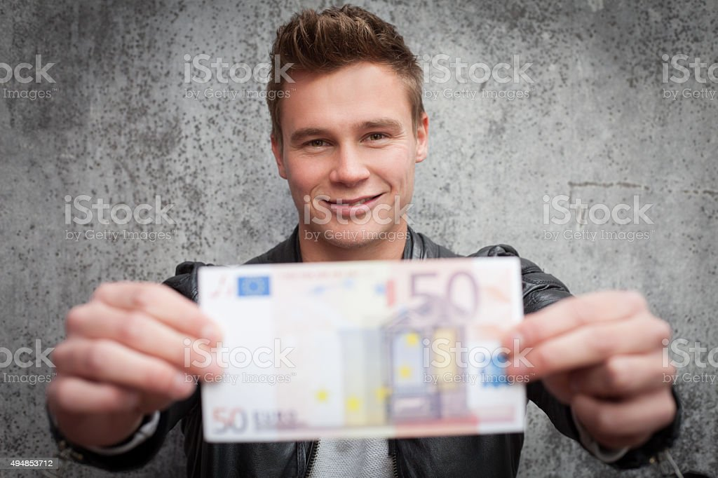 Attractive young guy holding fifty euro note stock photo