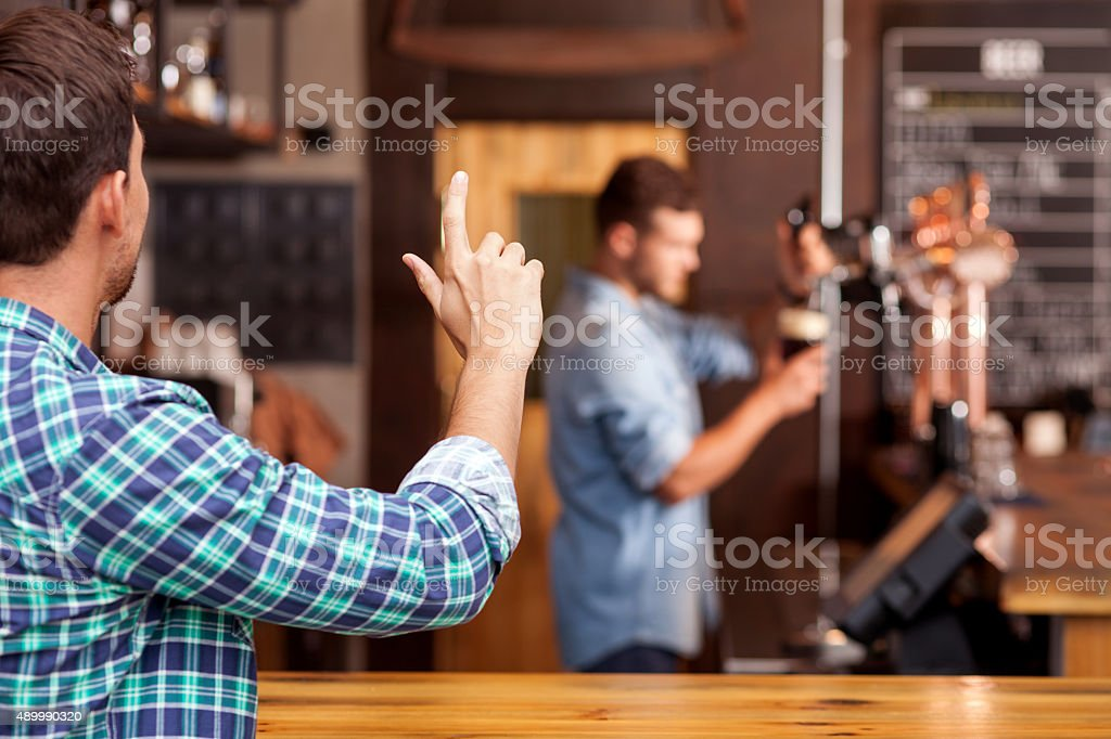 Attractive young guy orders lager in pub stock photo