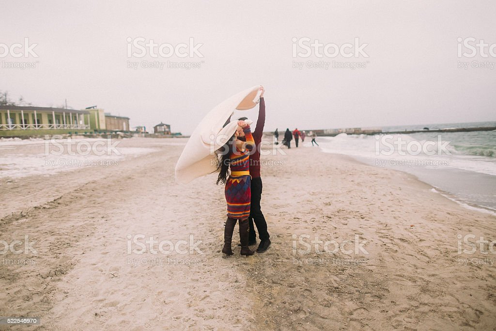 Attractive young happy couple kissing under white blanket on the stock photo