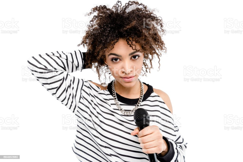 Attractive young heavy metal singer holding microphone and smiling at camera stock photo