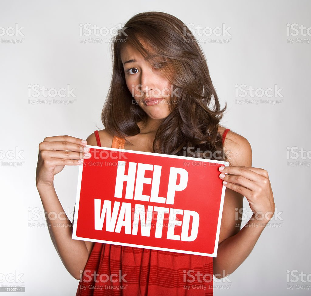 Attractive young Hispanic woman holds up 'Help Wanted' sign royalty-free stock photo