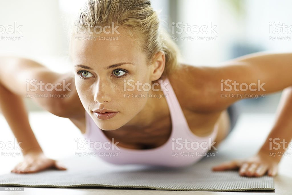 Attractive young lady doing push ups on exercise mat royalty-free stock photo