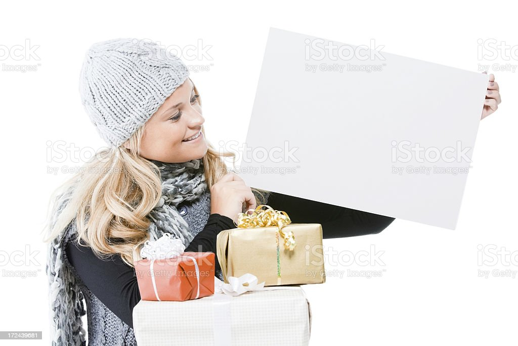 Attractive young lady with gifts holding a blank signboard royalty-free stock photo