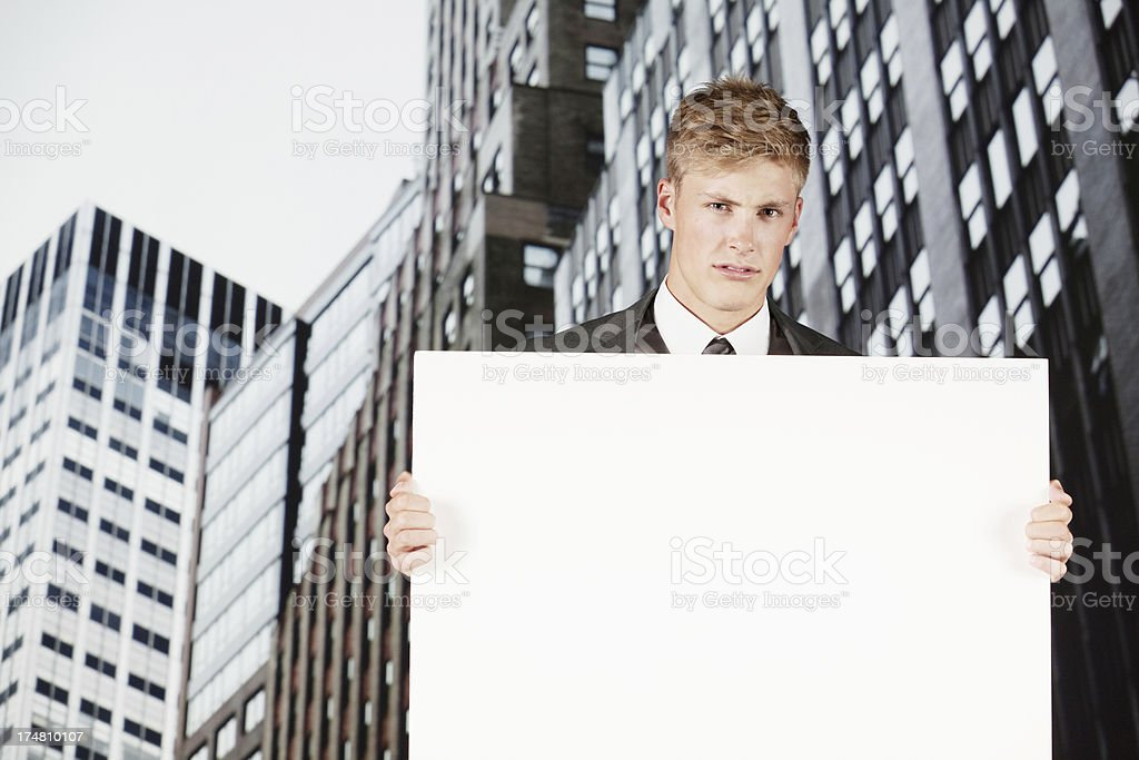 Attractive young male holding a blank signboard royalty-free stock photo