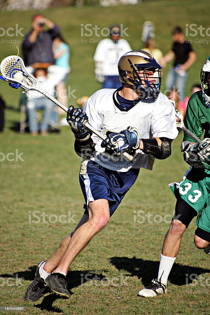 Attractive Young Male Lacrosse Player Lunges Agressively with Ball stock photo