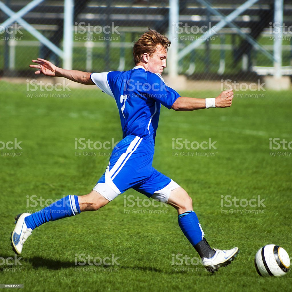 Attractive Young Male Soccer Player Sprints into Ball Kick royalty-free stock photo