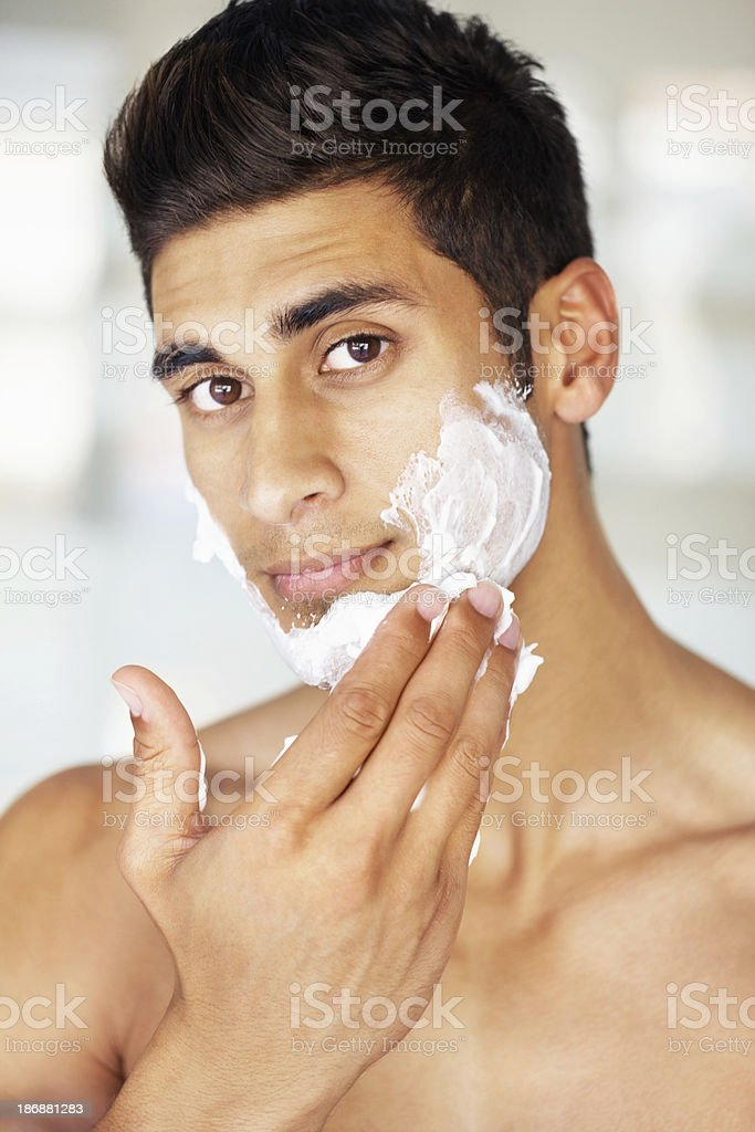 Attractive young man applying shaving cream to face royalty-free stock photo