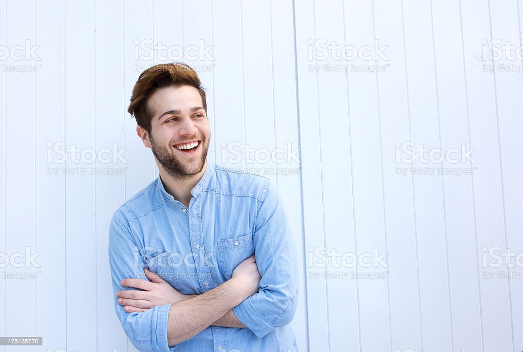 Attractive young man laughing with arms crossed stock photo