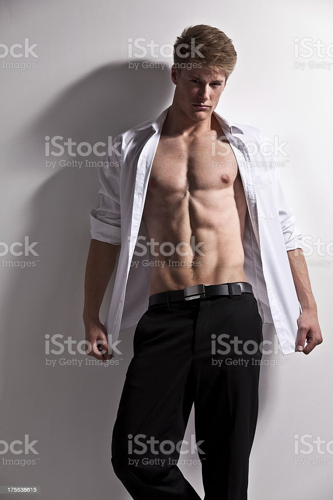Attractive young man leaning against a wall stock photo