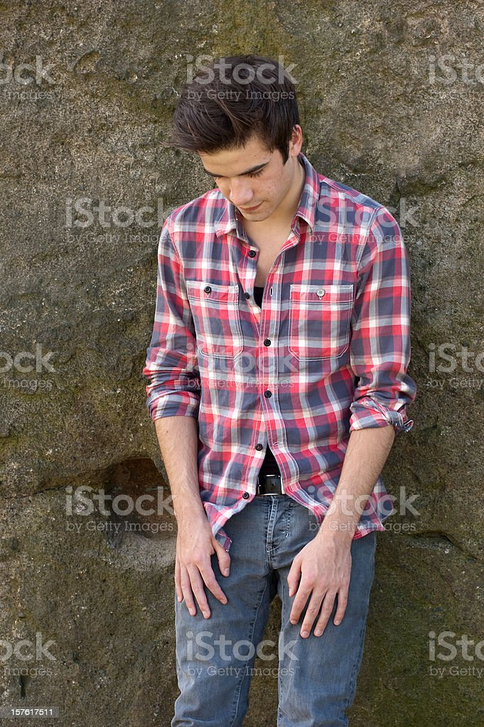 Attractive young man leaning against rock face royalty-free stock photo