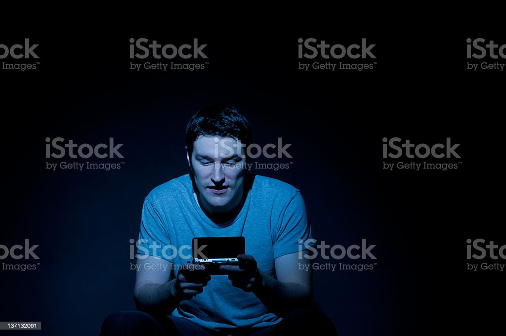 Attractive Young Man Playing Video Game in Dark Room royalty-free stock photo