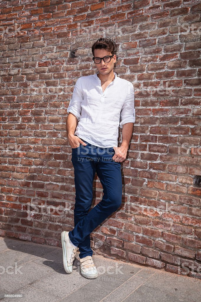 Attractive young man posnig with his hands in pockets stock photo