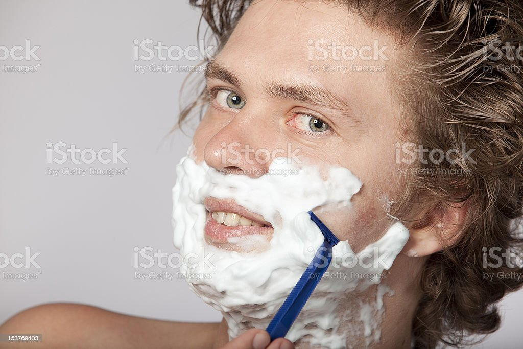 Attractive young man shaving with razor royalty-free stock photo