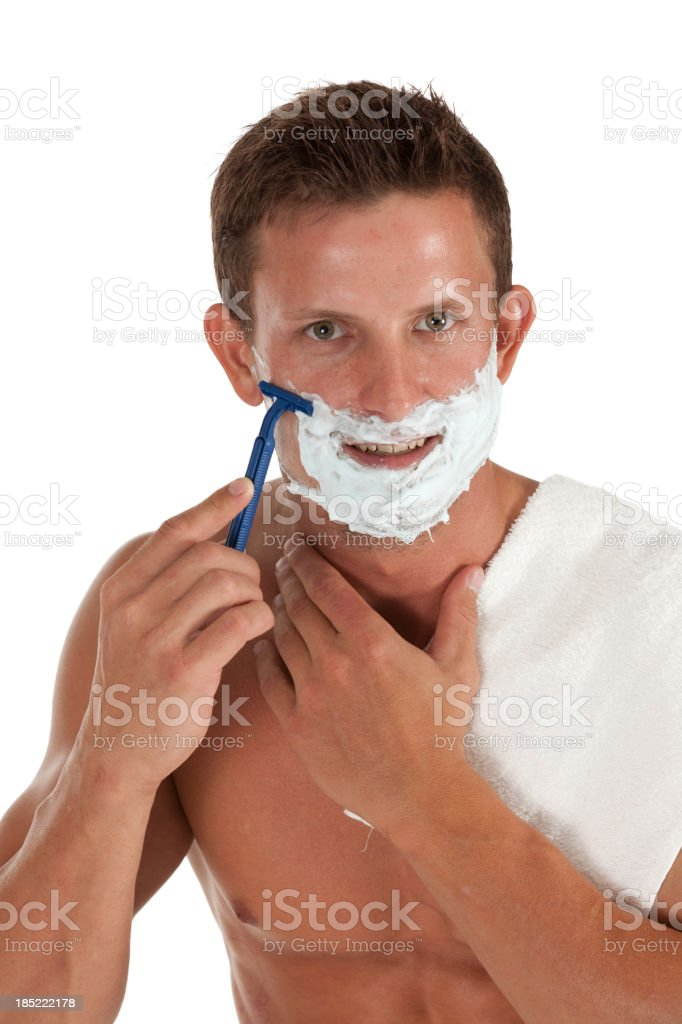 Attractive young man shaving with the use of razor royalty-free stock photo