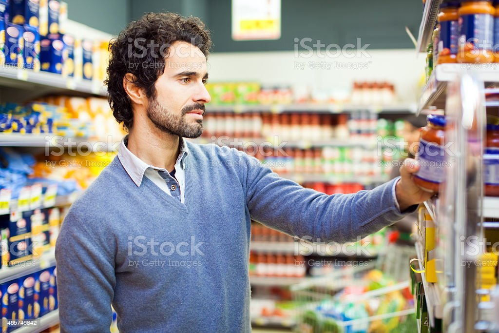 Attractive young man shopping in a supermarket stock photo