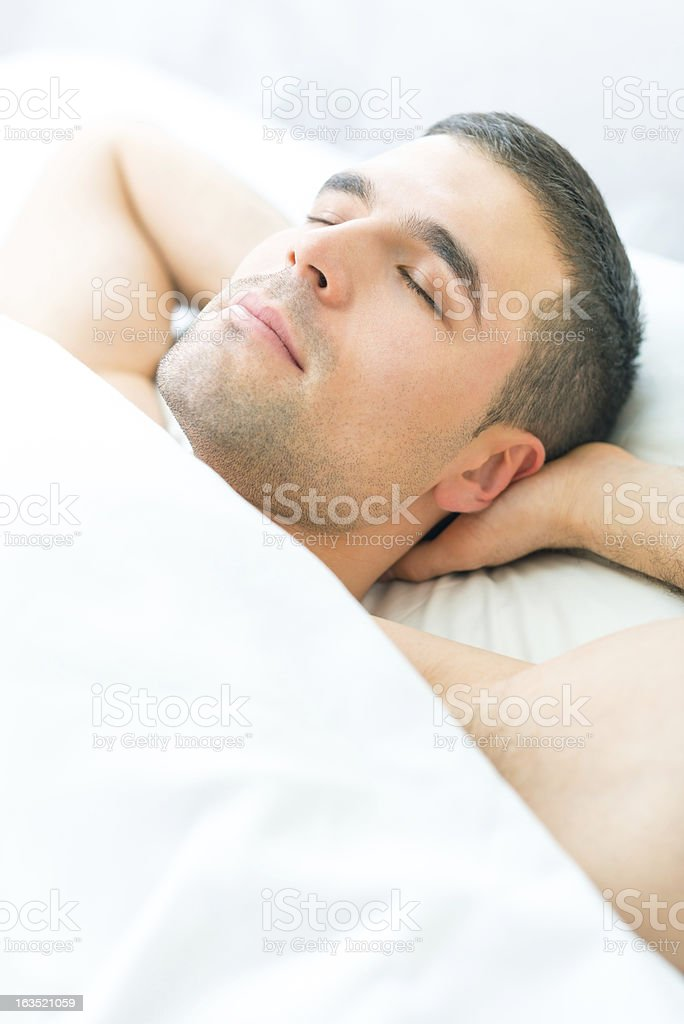 Attractive young man sleeping  in a soft bed sheets. royalty-free stock photo