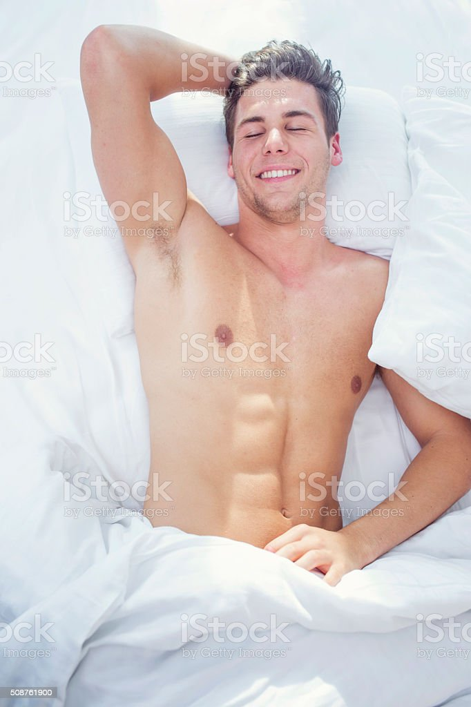 Attractive young man sleeping in bed stock photo