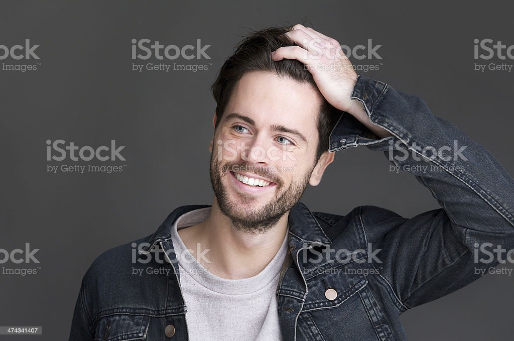 Attractive young man smiling with hand in hair stock photo