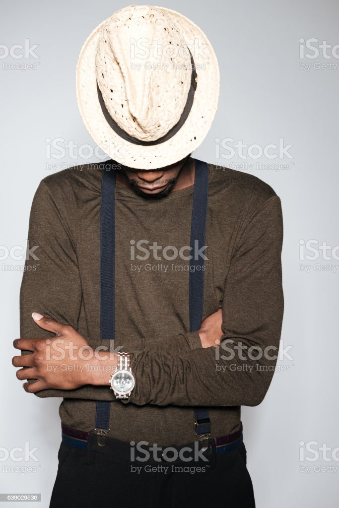 Attractive young man wearing hat standing in studio. stock photo