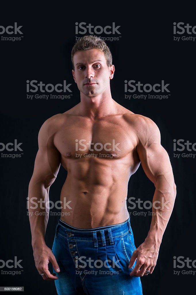 Attractive young man with naked muscular torso, wearing jeans stock photo