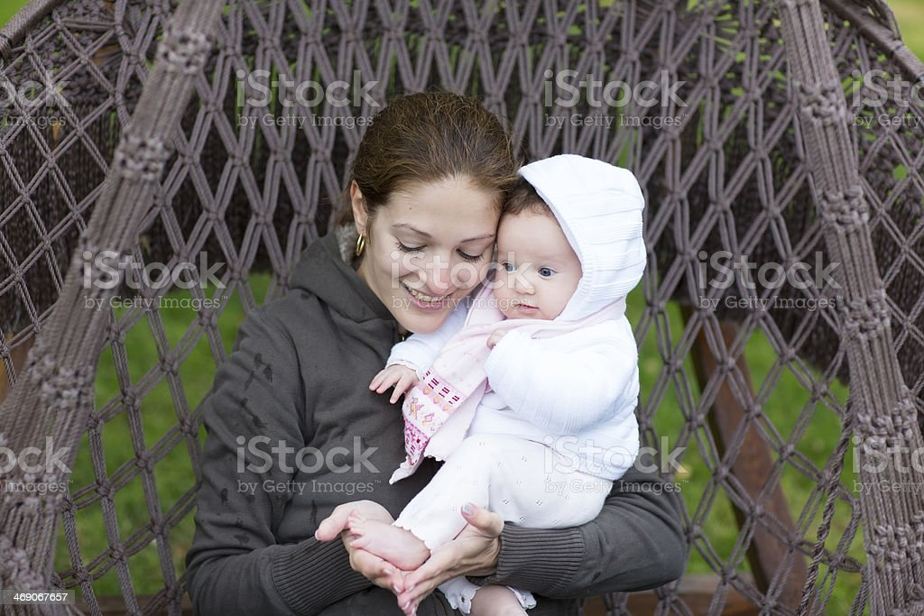 Attractive young mother playing with baby feet in a hammock royalty-free stock photo