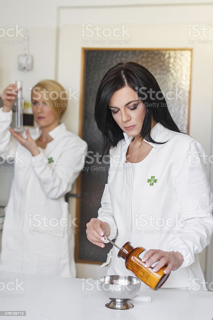Attractive young pharmacist preparing medication royalty-free stock photo