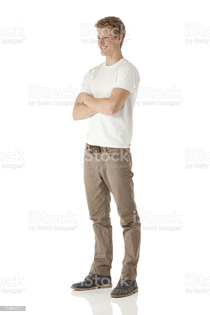 Attractive young smiling man standing with his arms crossed royalty-free stock photo