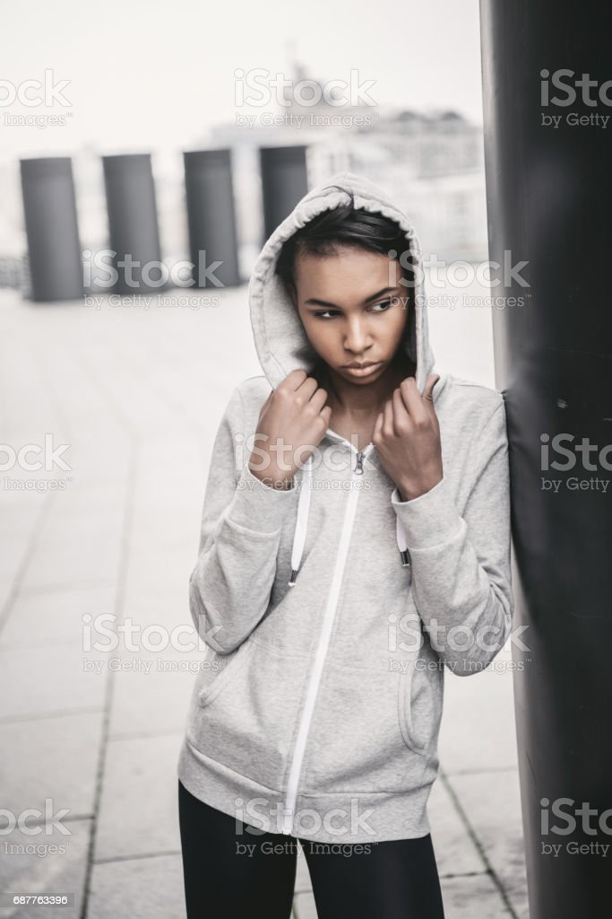 Attractive young sportswoman in hood posing on stadium and looking away stock photo
