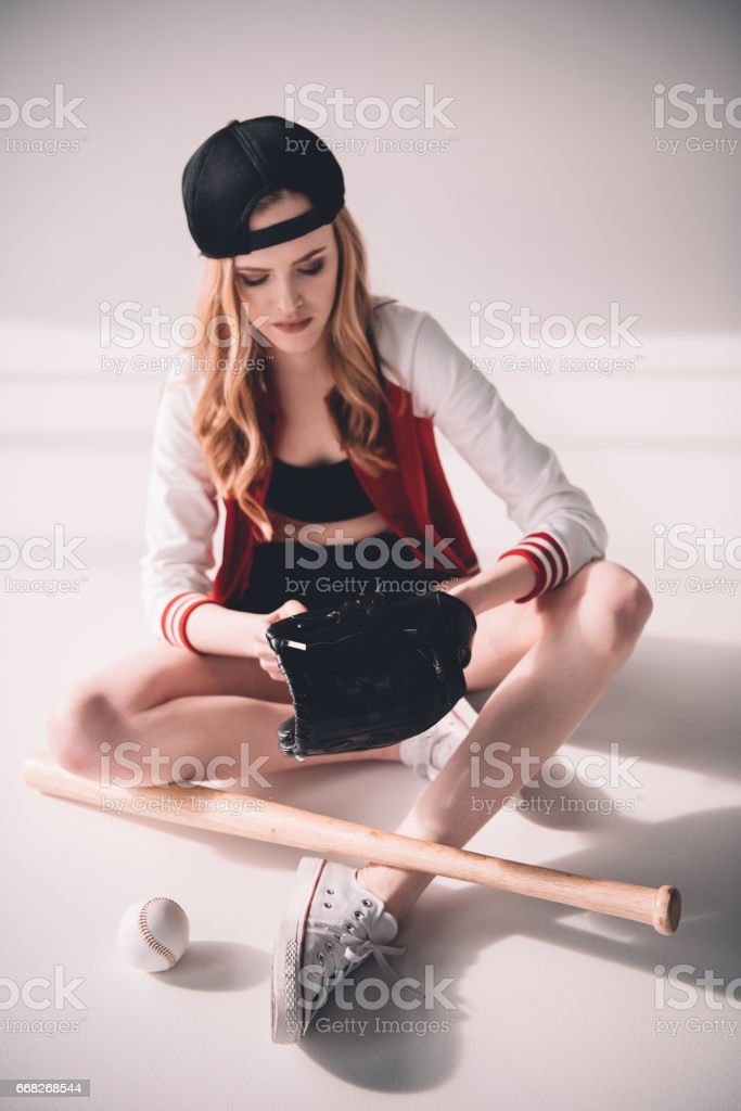 Attractive young sporty woman in cap sitting with baseball equipment stock photo