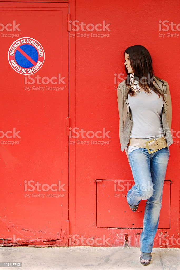 Attractive young woman against red wall stock photo