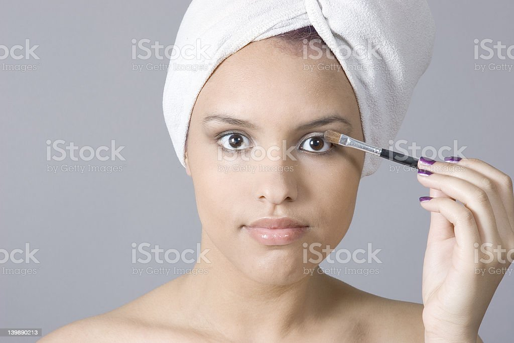 Attractive young woman applying makeup royalty-free stock photo