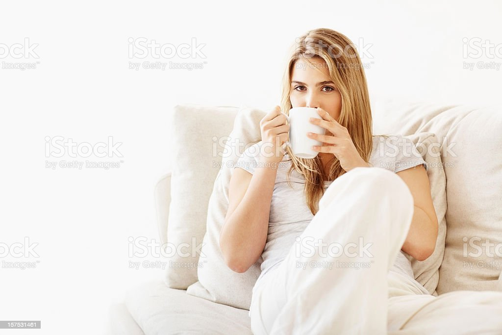Attractive young woman drinking coffee in couch royalty-free stock photo