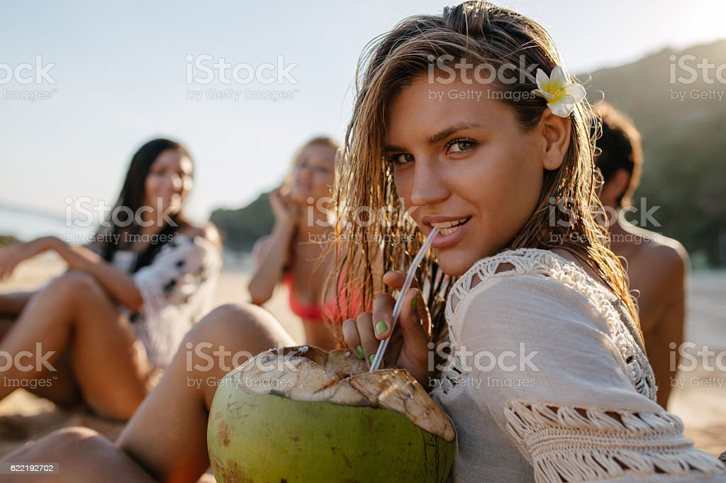 Attractive young woman drinking fresh coconut stock photo