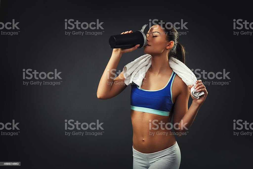 Attractive young woman drinking proteins stock photo