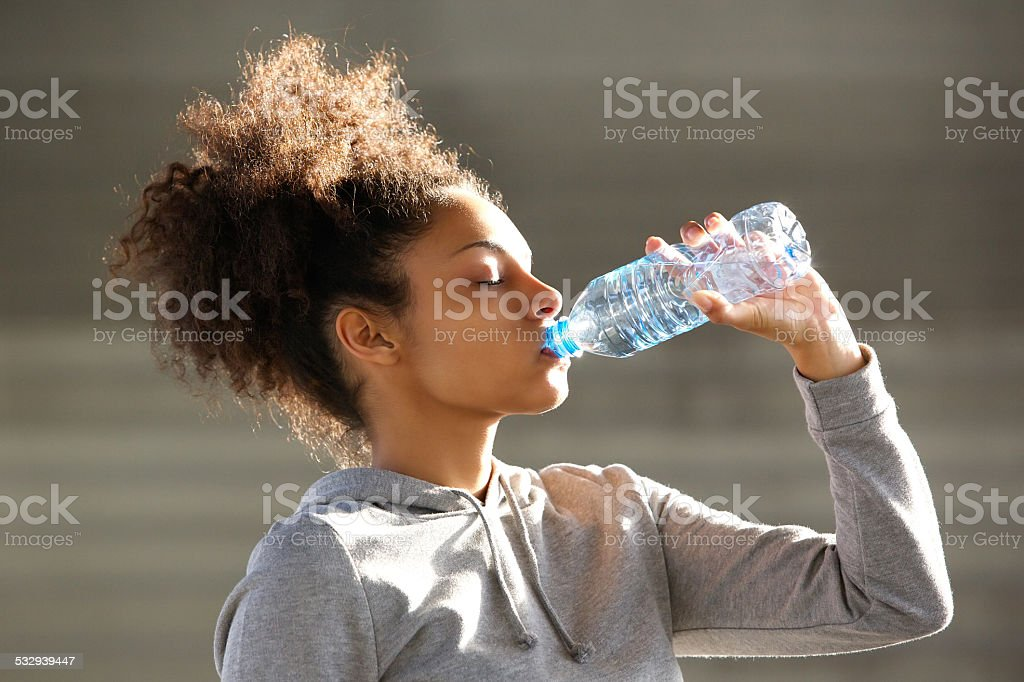 Attractive young woman drinking water from bottle stock photo