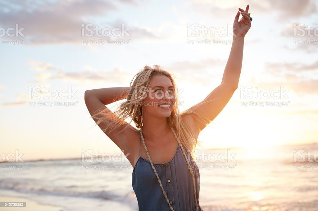 Attractive young woman enjoying on the beach at sunset stock photo