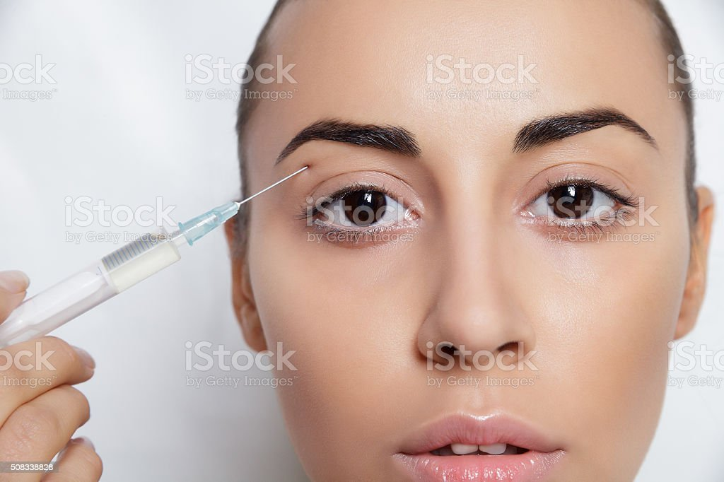 Attractive young woman gets cosmetic injection stock photo