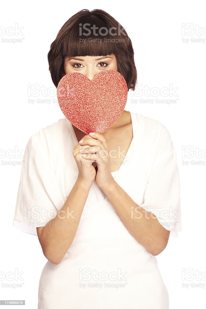 Attractive Young Woman Hiding Behind a Red Heart Cutout royalty-free stock photo