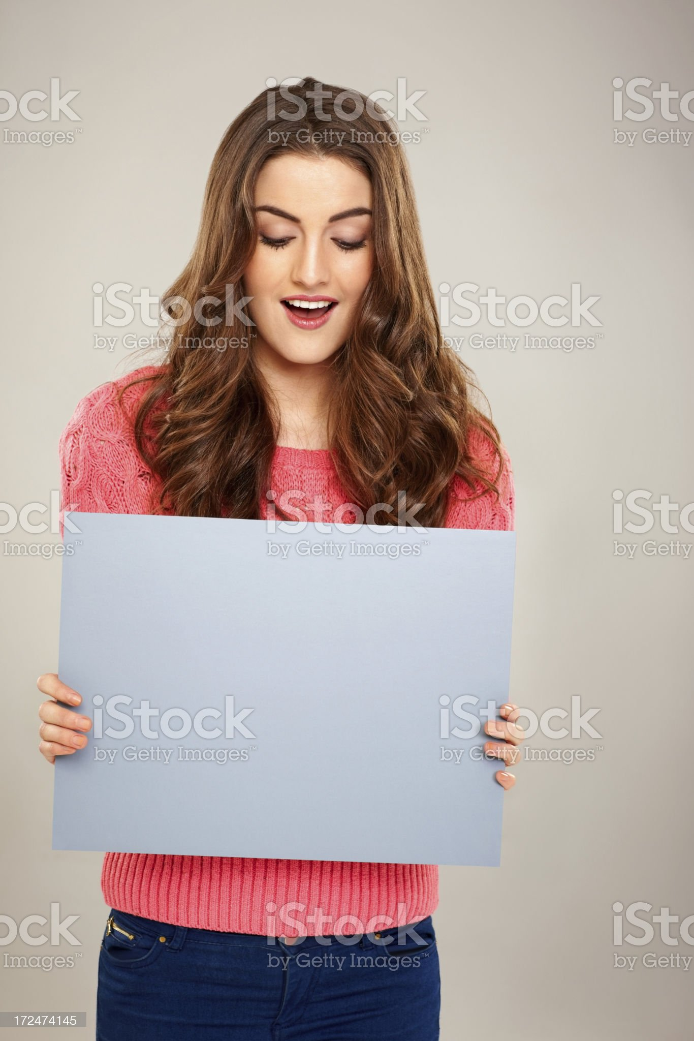 Attractive young woman holding a empty placard over grey background royalty-free stock photo