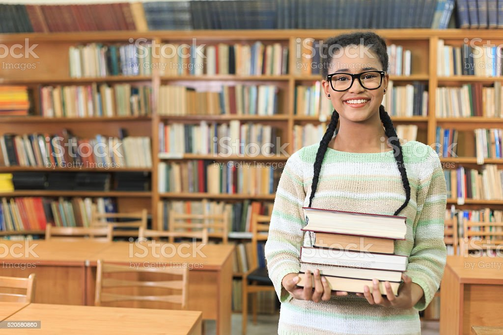 Attractive young woman holding stack of books in the library stock photo