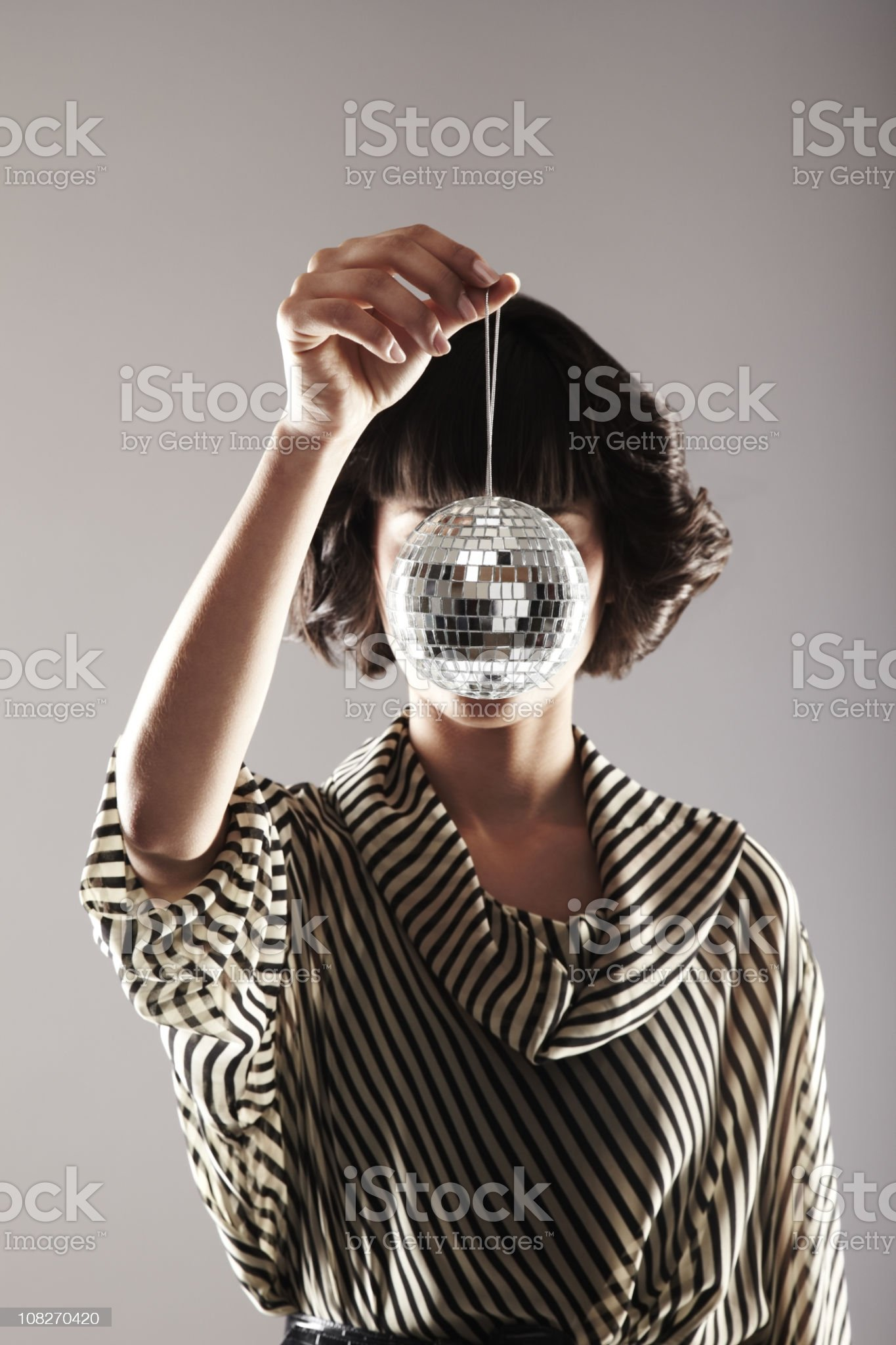Attractive Young Woman Holding Up a Disco Ball royalty-free stock photo