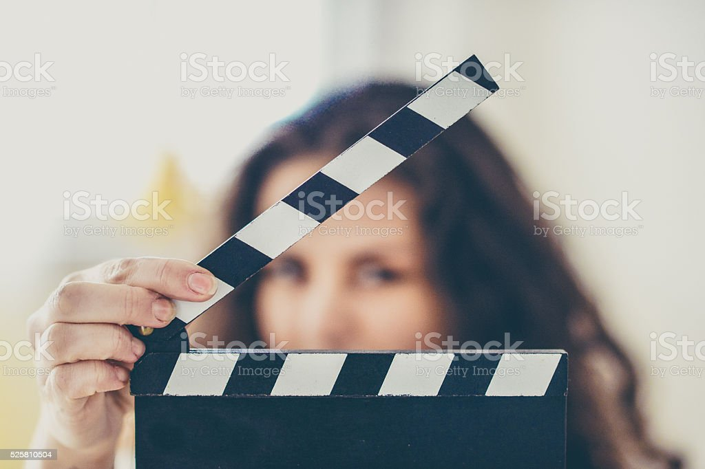 Attractive young woman holds an open film slate stock photo