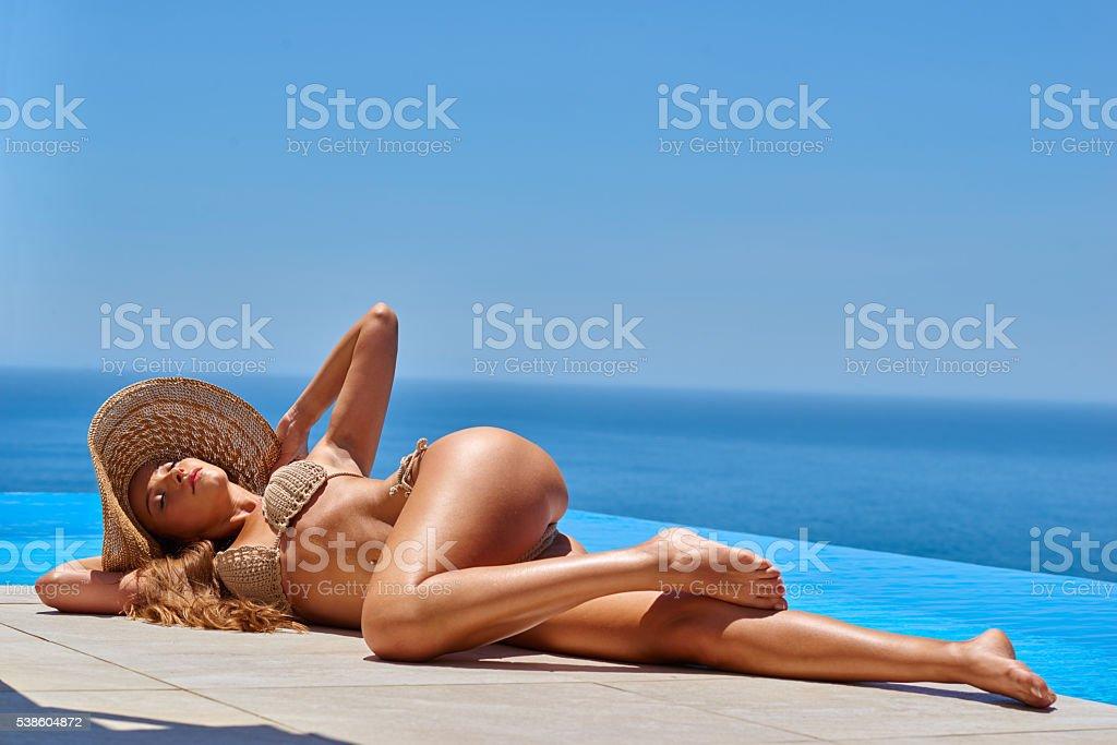 Attractive young woman in bikini near swimming pool stock photo
