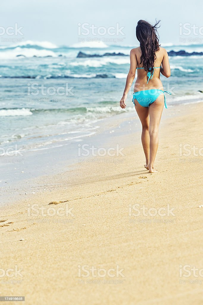 Attractive Young Woman in Blue Bikini Walking on Hawaiian Beach royalty-free stock photo