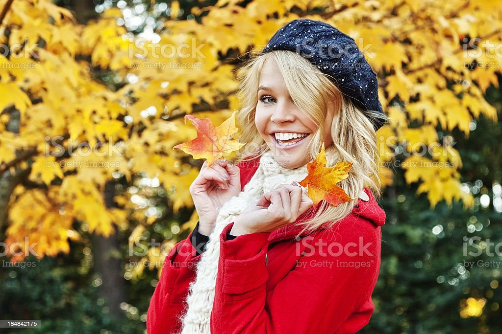 Attractive Young Woman in Fall Fashion with Colorful Leaves royalty-free stock photo